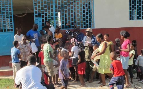 Men distributing supplies to kids